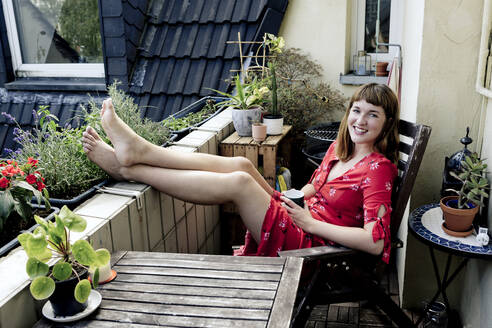 Portrait of smiling young woman relaxing with cup of coffee on balcony - FLLF00257