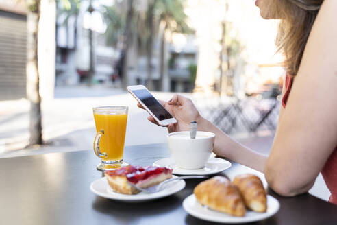 Young woman sitting at street cafe using cell phone - AFVF03627