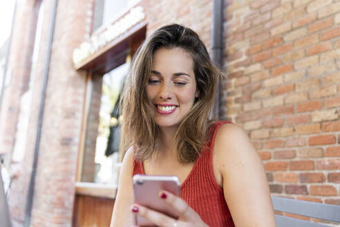 Portrait of smiling young woman looking at cell phone - AFVF03636