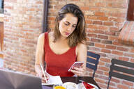 Young blogger sitting at street cafe making notes while looking at smartphone - AFVF03642