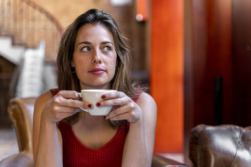 Portrait of young woman with cup of coffee - AFVF03645