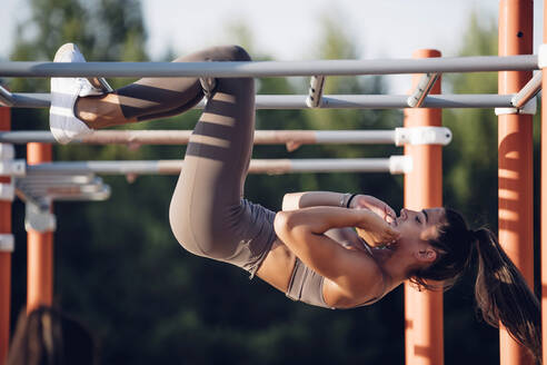 Young woman doing workout on calisthenics bars - OCMF00539