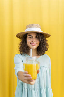 Portrait of woman with straw hat, drinking juice, yellow background - AFVF03665