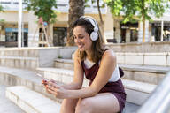 Young woman using smartphone and listening music - AFVF03683