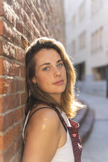 Young woman leaning on brick wall and looking at camera - AFVF03701
