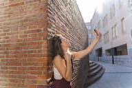 Young woman leaning on brick wall, taking a selfie - AFVF03707
