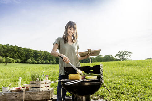 Smiling woman preparing vegetable on barbecue grill - FMKF05795