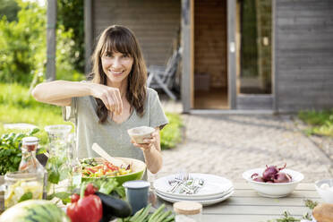 Portrait of smiling woman preparing a salad on garden table - FMKF05804