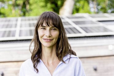 Portrait of smiling woman in front of a house with solar panels on the roof - FMKF05819