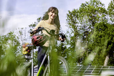 Smiling woman pushing bicycle with organic fruit on a meadow - FMKF05825