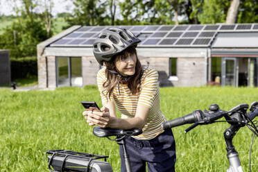 Smiling woman with bicycle and cell phone on a meadow in front of a house - FMKF05828