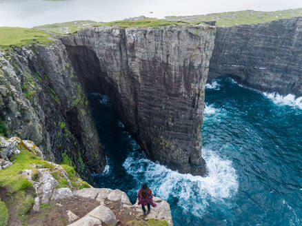 Aerial view of woman standing on the edge of tourists English Slave cliff, Faroe island. - AAEF00648