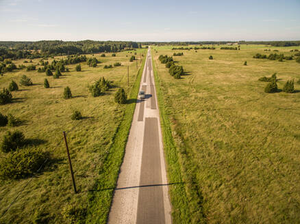 Aerial view of a car driving on a road in the countryside in Estonia. - AAEF00927