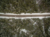 Aerial view of cars driving across a snowy forest in Estonia - AAEF00948