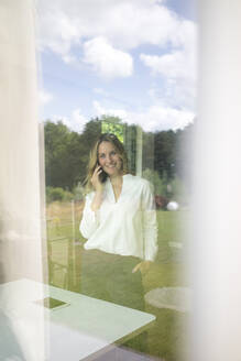 Smiling businesswoman talking on the phone at home behind windowpane - MOEF02412