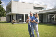 Portrait of happy family of three standing in garden of their home - MOEF02424