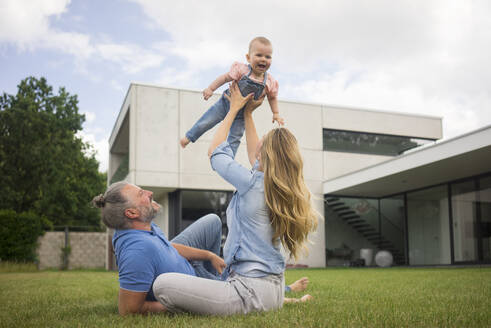 Happy mother with father lifting up baby girl in garden - MOEF02427