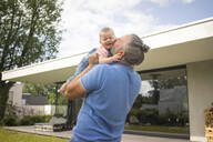 Happy mature man holding baby girl in garden of his house - MOEF02433
