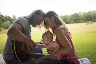 Father, mother and baby girl sitting outdoors with guitar - MOEF02442