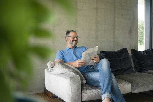 Smiling mature man sitting on couch at home reading newspaper - MOEF02448