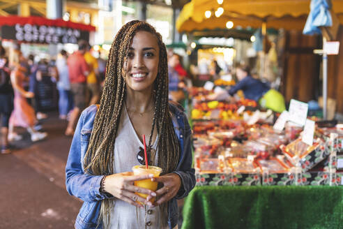 Portrait of happy young woman with fresh orange juice on street market, London, UK - WPEF01681