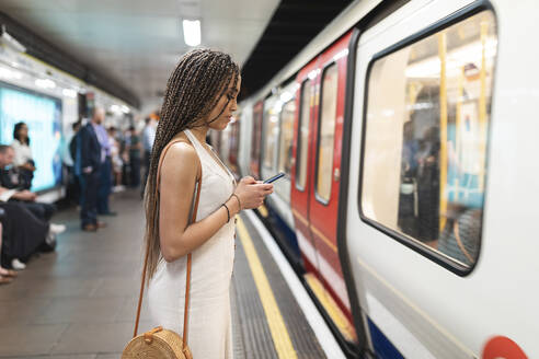 Young woman waiting at subway station platform looking at cell phone, London, UK - WPEF01693