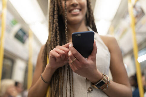 Happy woman looking at cell phone in underground train, London, UK - WPEF01696