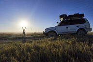 Woman standing with arms raised by off-road vehicle at Makgadikgadi Pans, Botswana - VEGF00442