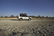 White off-road vehicle with baobab trees in background against clear sky, Makgadikgadi Pans, Botswana - VEGF00445