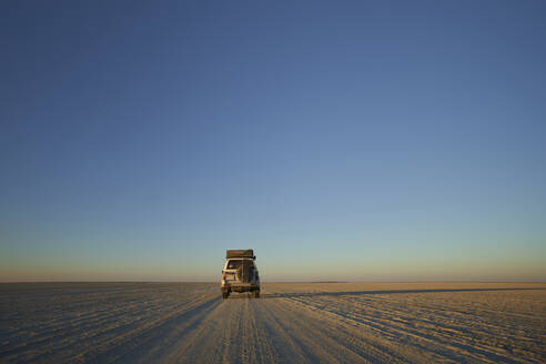 Off-road vehicle against clear sky, Makgadikgadi Pans, Botswana - VEGF00451