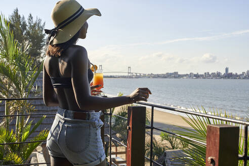 Young woman with a drink at the waterfront looking at the skyline of Maputo, Mozambique - VEGF00457
