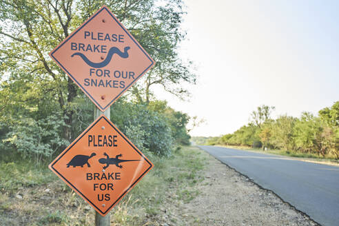 Beware of snakes, turtles and lizards sign at the roadside, Marloth Park, South Africa - VEGF00469