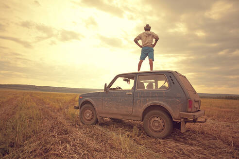 Mari man standing on car roof in rural field - BLEF13818