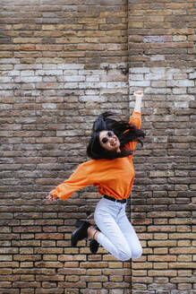 Asian woman jumping, brick wall in the background - LJF00620