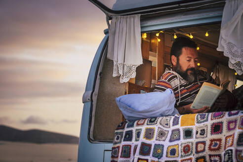 Mature man lying in van and reading a book - SIPF02057