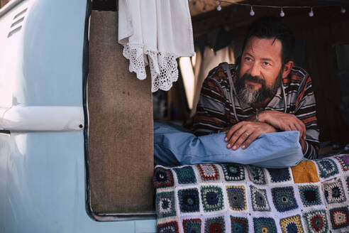Mature man lying in van - SIPF02081