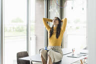 Smiling young businesswoman sitting on table in office looking up - UUF18474