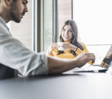 Young businesswoman and businessman sitting at desk in office talking - UUF18483