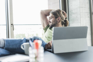 Young businessman sitting at desk in office thinking - UUF18507