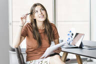 Young businesswoman sitting at desk in office taking notes - UUF18513