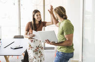 Happy young businesswoman and businessman high fiving in office - UUF18519