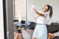 Young businesswoman in office taking a selfie - UUF18525