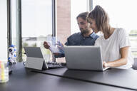 Young man and woman working together at desk in office - UUF18543