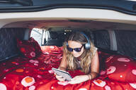 Pretty blonde woman with sunglasses and headphones in camping inside a van using tablet - OCMF00562