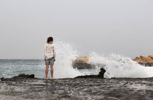 Rear view of man standing at seafront, Gulf of Oman, near Sur, Oman - WWF05150
