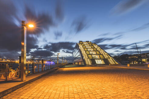 Diminishing perspective of footpath by Dockland building against sky at dusk, Hamburg, Germany - KEBF01286
