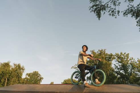 Young man with BMX bike at skatepark having a break - AHSF00740