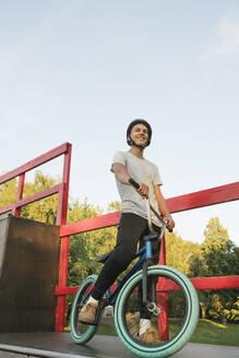 Young man with BMX bike at skatepark having a break - AHSF00749