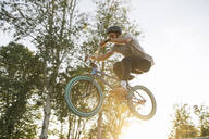 Young man jumping with BMX bike at sunset - AHSF00752