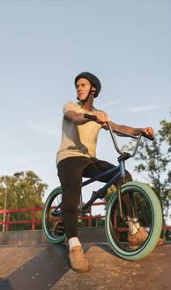 Young man with BMX bike at skatepark having a break - AHSF00761